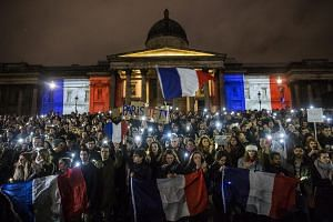 Hundreds of people attend a vigil for the victims of the Paris attacks in Trafalgar Square, Britain.