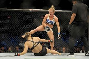 MMA fighter Holly Holm stands over opponent Ronda Rousey after knocking her to the canvas during their UFC bantamweight bout at Etihad stadium in Melbourne, on Nov 15, 2015.