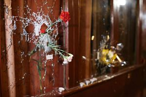 A flower hangs out of a bullet hole in a window on Rue Alibert in Paris, France, on Nov 14, 2015.