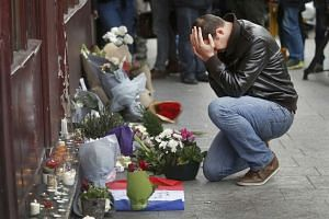 A man pays his respect outside the Le Carillon restaurant.