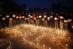 Nepalese journalists and sports personalities participate in a candlelight vigil for the victims of the Nov 13 Paris attacks in Nepal.