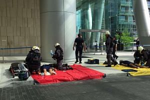SCDF front-line firefighters attending to the victims at One Marina Boulevard during one of the scenarios simulating a chemical agent attack.