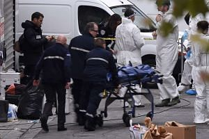 A body is removed from the apartment in the northern Paris suburb of Saint-Denis, on Nov 18, 2015, hunting those behind the attacks that claimed 129 lives in the French capital.