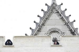 French police snipers securing the area from the roof of a church in the northern Paris suburb of Saint-Denis yesterday, after special forces had carried out a raid on an apartment.