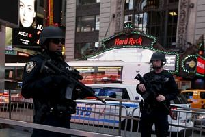 Armed New York City police officers with the special operation division Strategic Response Group stand in front of the US Armed Forces Career Center at Times Square in New York Nov 18, 2015.