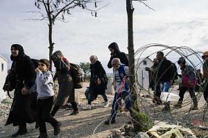 Migrants and refugees cross the Greek-Macedonian border near Gevgelija on Nov 15, 2015.