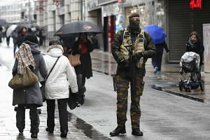 A soldier patrols outside a shopping center in Brussels on Nov 21, 2015.