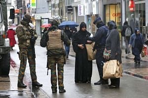 Belgian soldiers and a police officer control the documents of a woman in a shopping street in central Brussels.