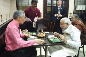 Indian Prime Minister Narendra Modi, PM Lee Hsien Loong and Ms Ho Ching (hidden) having their meal at Komala Vilas. An interpreter is seated slightly behind Mr Modi.