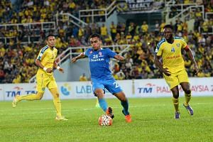 LionsXII's Sufian Anuar (middle in blue), takes on Pahang's Damion Stewart (right) and Saifulnizam Miswan (left) during their Malaysia Cup football match.