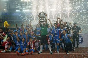 LionsXII goalkeeper Izwan Mahbud lifting the Malaysian FA Cup trophy as the team celebrated its victory over Kelantan in Kuala Lumpur's Bukit Jalil National Stadium in May. Players have been left scrambling for fresh contracts after the FAM's decisio
