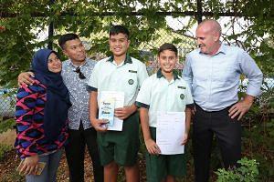 (From left) Madam Nur Aryana Aziz; her husband, Mr Sadri Farick; their son, Emyr Uzayr; Jayden Francis, and his father, Mr Dannie Francis, at Tanjong Katong Primary School yesterday.