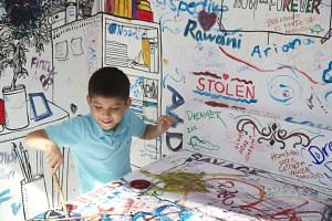 A visitor doodling in Speak Cryptic's Kamar Kamillion artwork in Singapore: Inside Out.