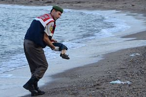 A Turkish police officer carries Aylan's dead body off the shores in Bodrum, southern Turkey.