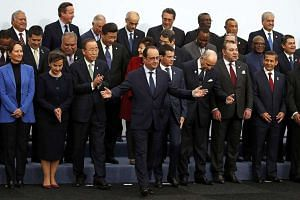 French President Francois Hollande (centre) gathering with world leaders for a group photo on the opening day of the United Nations Climate Change Conference 2015 at Le Bourget, near Paris, yesterday. As host, Mr Hollande told the world leaders that