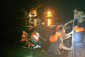 Passengers of a Singapore-bound ferry from Batam, who were evacuated after the vessel hit a floating object, being helped by villagers after water began entering their lifeboat. The villagers came to the rescue on Sunday night, after 97 people were e