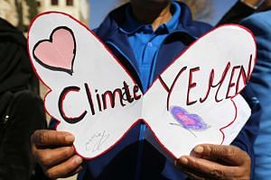 A Yemeni holds a placard as he participates in the Global March for Climate.