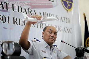 The head of Indonesia's National Transportation and Safety Committee, Mr Soerjanto Tjahjono, holding a model plane during a news conference to announce the findings in the investigation of the AirAsia QZ8501 crash, on Dec 1, 2015.