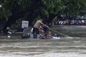 Indian policemen rescue people from flood waters in Chennai.