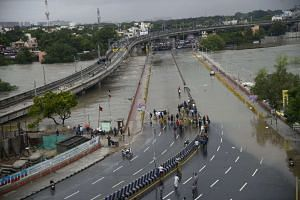 People make their way along a flooded road in Chennai, India.