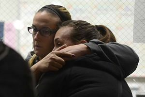 Evacuees at the Inland Regional Center hug each other as they wait inside the Rudy C Hernandez Community Center in San Bernardino, California, on Dec 2015.