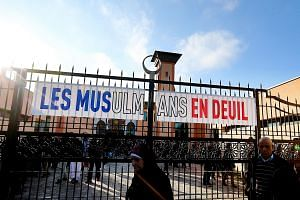 """People walk past a banner that reads """"Muslims in mourning"""" as they leave the Reims mosque after the Friday prayer on Nov 27."""