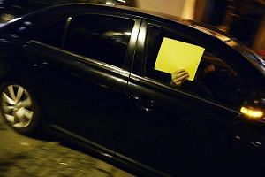A person hiding behind a folder in a police car near the Baur au Lac hotel in Zurich yesterday, the scene of the dawn raids. Fifa said it will continue to cooperate fully with investigations after police arrested its officials - Juan Angel Napout (be