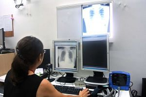 Dr Cynthia Chee, senior consultant and respiratory physician at Tan Tock Seng Hospital's Tuberculosis Control Unit (TBCU), examining an x-ray of a TB patient's lungs at the TBCU.