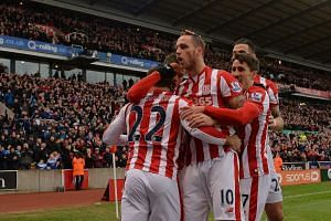 Stoke City's Austrian striker Marko Arnautovic (centre) celebrates with teammates after scoring.