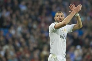 Karim Benzema applauds supporters as he leaves the pitch.