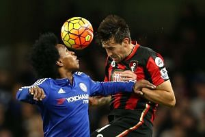 Bournemouth midfielder Charlie Daniels (right) jumps for a header with Chelsea midfielder Willian.