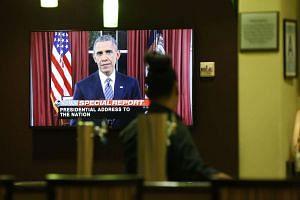 A bartender at a hotel near the Inland Regional Center watching the live telecast of President Barack Obama's address on Dec 6, 2015, in San Bernardino, California, USA.