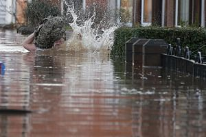 A local resident stumbles as he wades through flood water on a residential street in Carlisle, Britain on Dec 6, 2015.