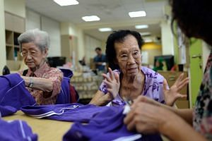 Madam Yong Yuet Thai (left) and Madam Tan Kim Soo snip off loose threads from T-shirts, and iron and pack them before they are delivered to customers, in a project aimed at helping seniors to stay productive.
