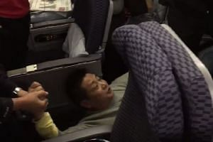Police officers attempting to drag the man off the plane.