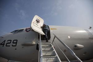 A US Navy officer enters a United States Navy P-8 Poseidon military aircraft displayed at the Singapore Airshow on Feb 10, 2014.