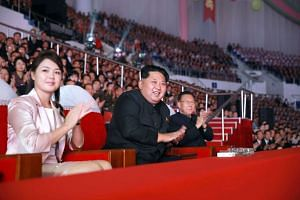 Kim Jong Un (centre), accompanied by his wife Ri Sol Ju, enjoying a performance.