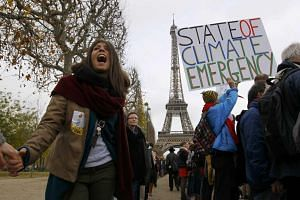 Environmentalists hold hands as they form a human chain near the Eiffel Tower in Paris on Dec 12, 2015.