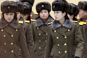 Members of the Moranbong Band of North Korea arrive at Beijing International Airport before departing from Beijing, China on Dec 12, 2015.