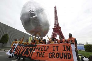 "Protestors with the message ""Divest. Keep it in the Ground"" asking investment funds to move their money out of fossil fuels at the COP21 in Le Bourget, near Paris, France, Dec 2, 2015."