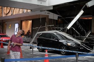 A black Volvo and a white Prime Royal taxi were caught under the roof of Hilton Singapore's driveway when it collapsed at close to 3pm yesterday. Four people were taken to hospital. Hilton regional general manager Peter Webster theorised that the pro