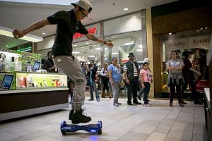 A stall owner performing tricks on a Power Board, a type of hoverboard he sells during Black Friday in Austin, Texas.