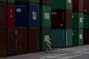 A man walks near cargo containers at a port in Tokyo, in this Jun 17, 2015 file photo.