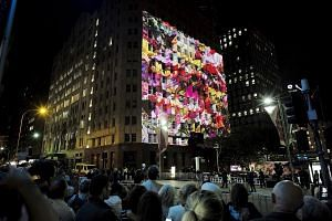 A giant photo of floral tributes to the victims of the Sydney cafe siege being projected onto the exterior wall of the Lindt Cafe during a memorial service yesterday marking the first anniversary of the incident.