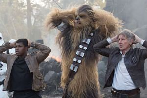 British actor John Boyega (far left), with Chewbacca and Harrison Ford, whom he says he has a cool relationship with.