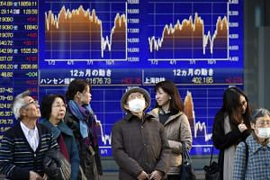 Pedestrians stand in front of a stock markets indicator board in Tokyo, Japan, 16 Dec 2015.