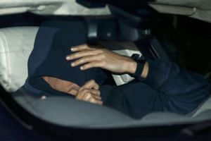 A man believed to be Jose Mourinho covers his face as he is is driven away from Chelsea.