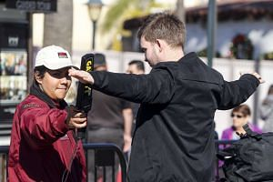 A security worker uses a metal-detecting wand to check a visitor at Universal Studios Hollywood.