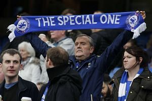 A Chelsea fan holds up a scarf in support of Mourinho.