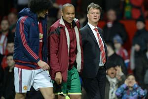 Van Gaal (right) leaving the pitch after his team's 2-1 loss to Norwich.